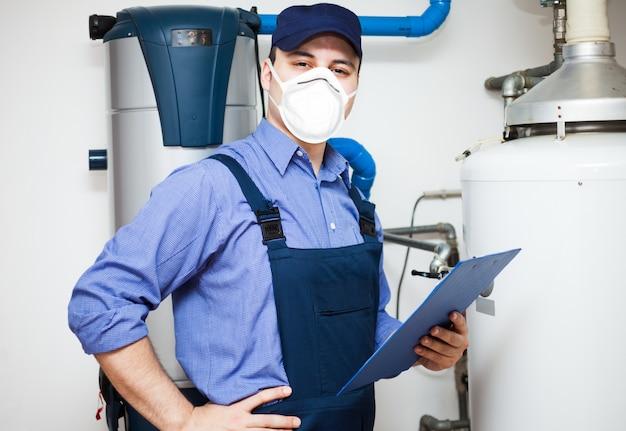 Technician servicing an hot-water heater during coronavirus pandemic Premium Photo