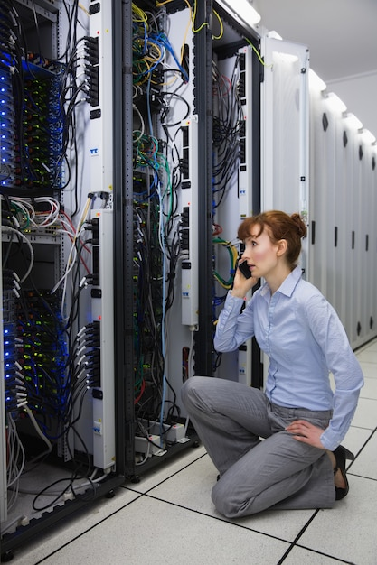 Technician talking on phone while analysing server Premium Photo