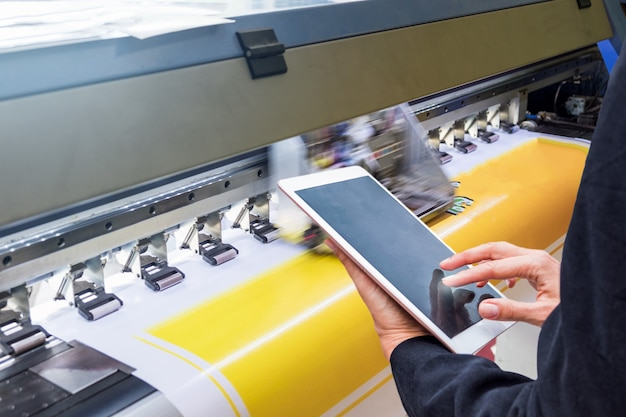Technician touch control tablet on format inkjet printer during yellow vinyl Premium Photo