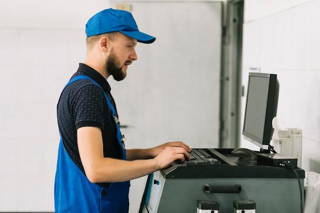Technician typing on keyboard at garage Free Photo