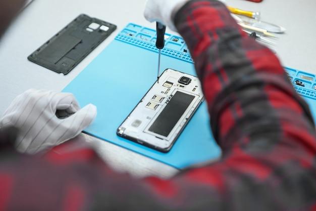 Техник в белых антистатических перчатках и клетчатой рубашке сидит за своим столом и с помощью точной отвертки откручивает винты на задней панели неисправного мобильного телефона Бесплатные Фотографии