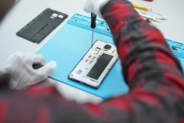 Technician wearing white antistatic gloves and plaid shirt sitting at his desk and using precision screwdriver to remove screws on back of faulty mobile phone Free Photo