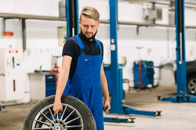 Technician with wheel in shop Free Photo