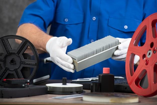 Technician with white gloves digitizing old 35mm film slide