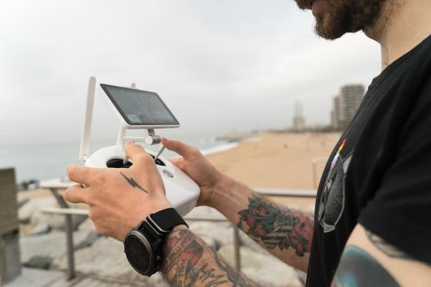 技術に精通したヒップスターまたは若い世代のミレニアル世代のプロの写真家は、リモコンを使用してドローンまたはクワッドコプターガジェットを空中で操縦します 無料写真