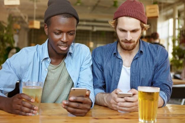 テクノロジー、オンライン通信、インターネット依存症。ハンサムなひげを生やした白人の男と彼のアフリカ系アメリカ人の友人またはパートナーがパブで新鮮なビールを楽しんでいると携帯電話でソーシャルネットワークを閲覧 無料写真