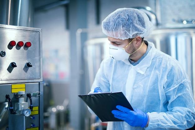 Эксперт-технолог в защитной униформе с сеткой для волос и маской, снимающей параметры с промышленного оборудования на предприятии по производству пищевых продуктов. Бесплатные Фотографии