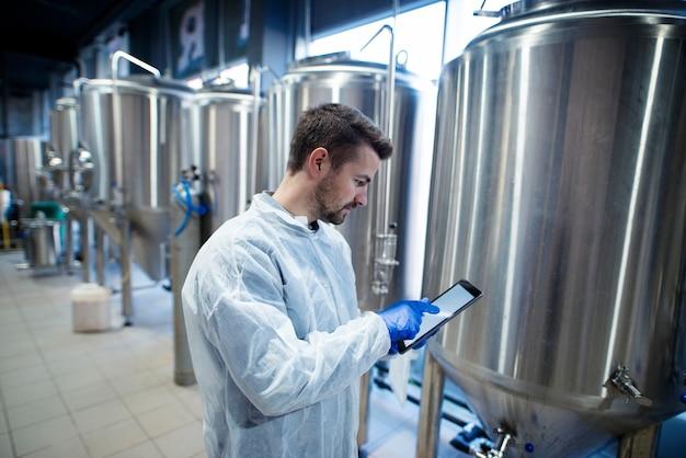 Эксперт-технолог стоит на заводе по производству продуктов питания и печатает на своем планшетном компьютере Бесплатные Фотографии