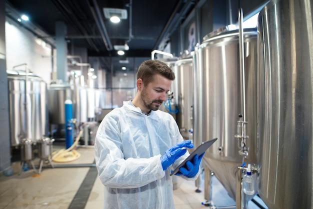 Esperto di tecnologo utilizzando computer tablet nella linea di produzione di fabbrica alimentare Foto Gratuite