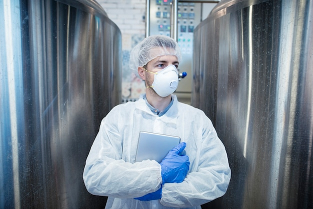 食品加工業界の金属製リザーバーのそばにタブレットを置いた保護服を着た技術者 無料写真