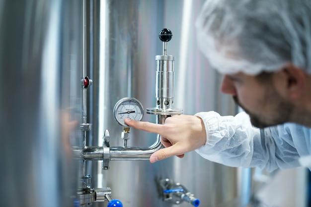 工場の産業機械の圧力計の圧力をチェックする白い防護服の技術者 無料写真