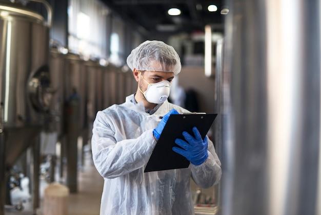 Технолог в белой форме проверки качества на заводе промышленного производства Бесплатные Фотографии