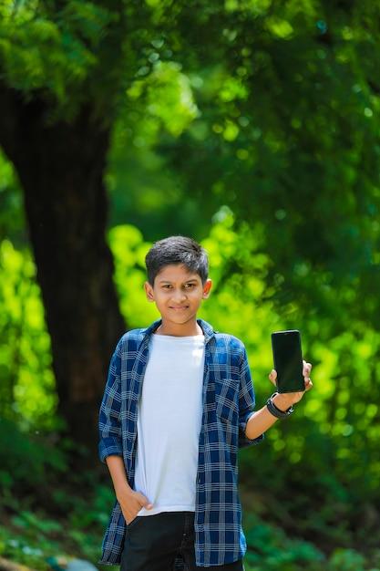Концепция технологии и людей - улыбающийся мальчик-подросток в синей рубашке, показывающий смартфон с пустым экраном Premium Фотографии