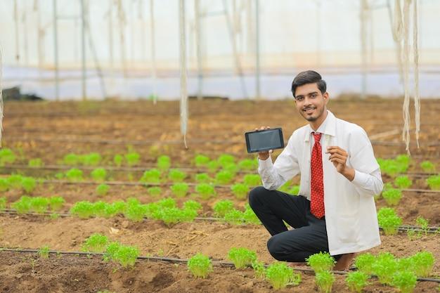 技術と人々の概念、温室でタブレットやスマートフォンを示す若いインドの農学者 Premium写真
