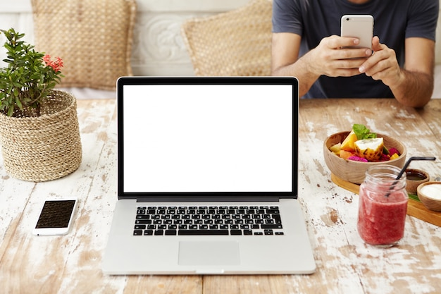 Technology, business, communication, people and advertisement. front view of wooden designer workplace with open laptop with blank screen, cell phone, glass of smoothie and bowl of fruits. Free Photo