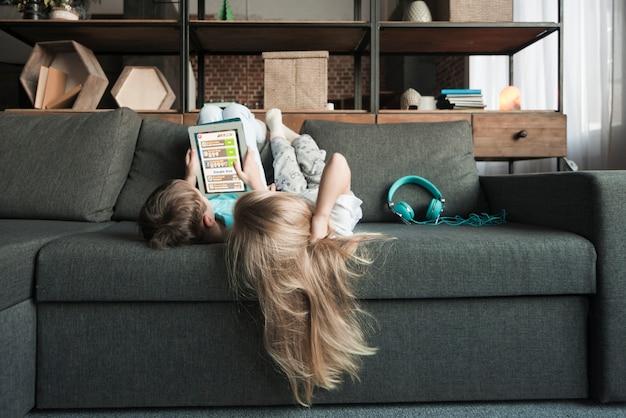 Концепция технологии с девушкой, лежащей на диване Бесплатные Фотографии