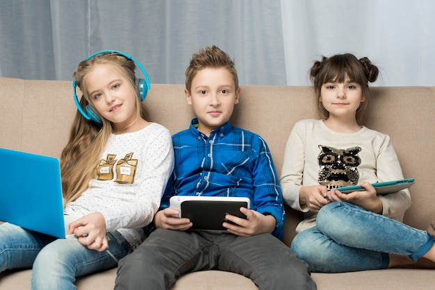 Technology concept with happy kids on couch Free Photo
