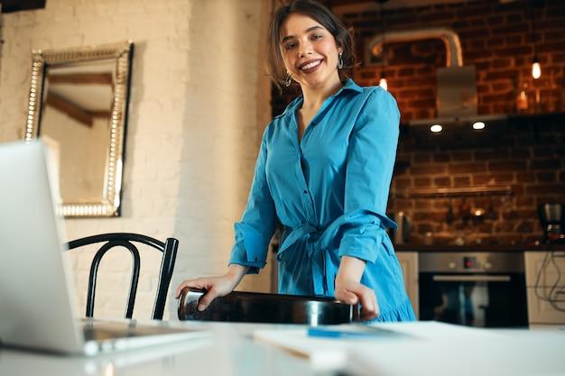 기술, 직업 및 원격 작업 개념. 부엌에 서 자신감 젊은 여성 카피라이터 무료 사진