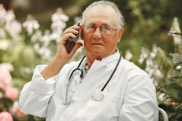 テクノロジー、人、コミュニケーションのコンセプト。サマーパークの年配の男性。電話を使っている医者。 無料写真
