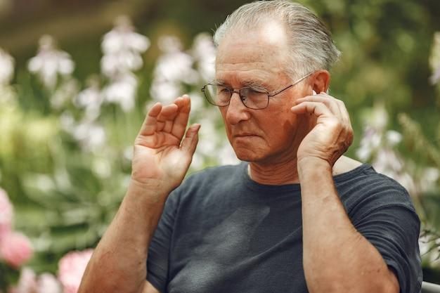 テクノロジー、人、コミュニケーションのコンセプト。サマーパークの年配の男性。電話を使用しているgrangfather。 無料写真