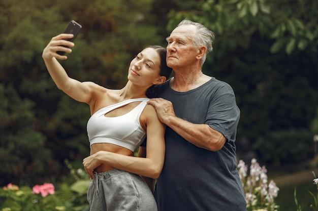 テクノロジー、人、コミュニケーションのコンセプト。サマーパークの年配の男性。孫娘とおじいさん。 無料写真
