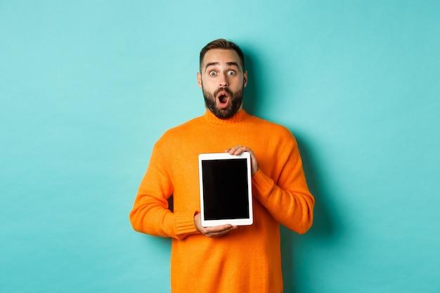 Tecnologia. mascella di caduta dell'uomo barbuto sorpreso, che mostra lo schermo della tavoletta digitale Foto Gratuite