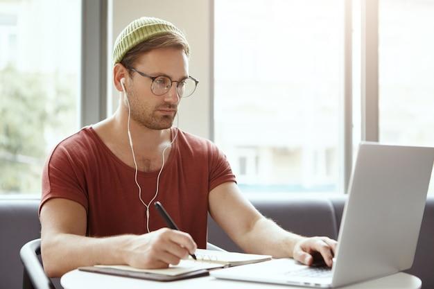 Технологии, работа и концепция работы. успешный переводчик-мужчина работает удаленно, пишет ручкой в блокноте Бесплатные Фотографии