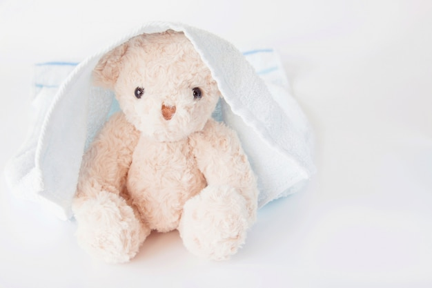 Teddy bear covered blue towel on white background, cute doll refreshing after bath Premium Photo