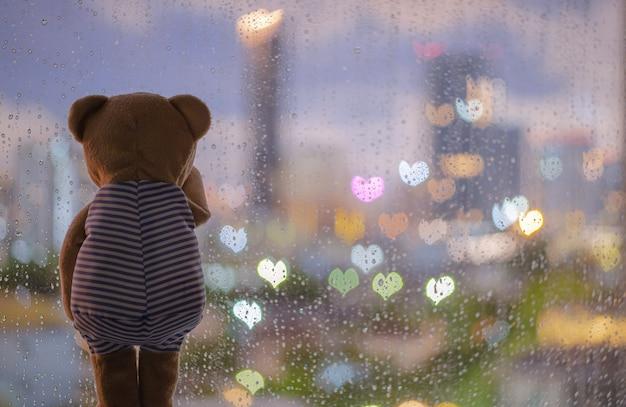 Плюшевый мишка плачет в одиночестве у окна во время дождя с красочными огнями боке в форме любви. Premium Фотографии