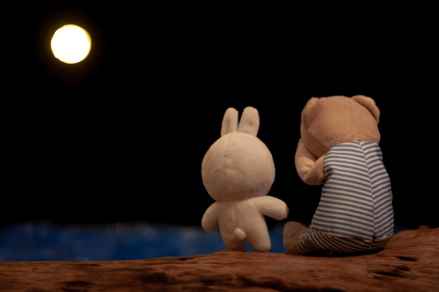 Teddy bear crying and rabbit doll giving consolation. Premium Photo