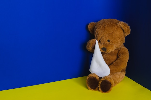 Teddy bear doll sitting at the corner and crying with handkerchief. child abuse concept. Premium Photo