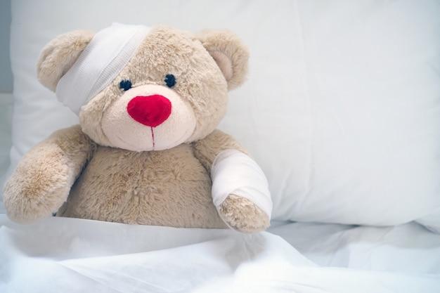 The teddy bear has gauze on the head Premium Photo
