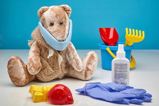 医療用マスク、ラテックス手袋、防腐剤、青い壁に散らばった子供のおもちゃのテディベア。コロナウイルスの第二波であるウイルス感染から子供を守るという概念 Premium写真