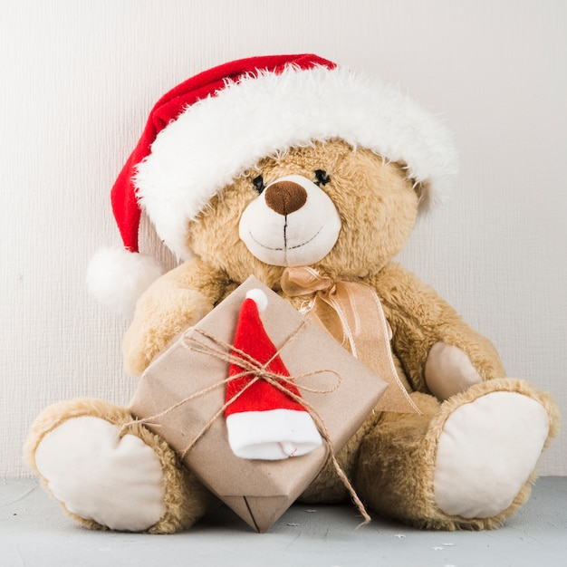 Teddy bear in santa hat with gift Free Photo