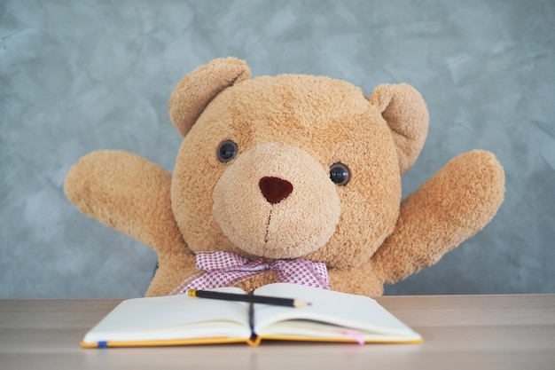 Teddy bear sit on the table and raise his hand Premium Photo