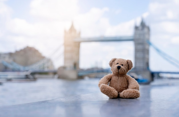 Teddy bear sitting alone with blurry london tower bridge background Premium Photo