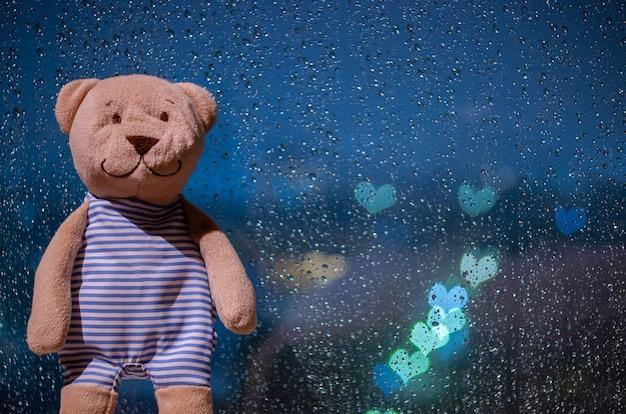 Плюшевый мишка стоит у окна во время дождя с красочными огнями боке в форме любви. Premium Фотографии