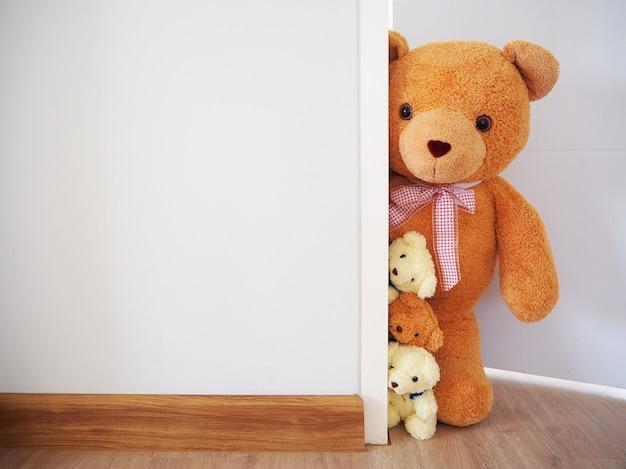 The teddy bear stood secretly behind the wall. Premium Photo