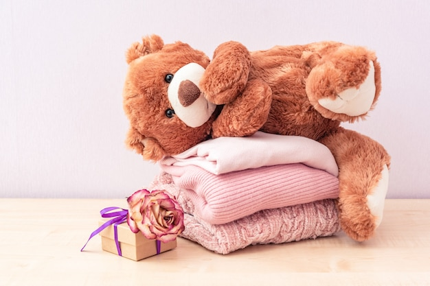 Игрушка плюшевый мишка и стопка вязаной женской одежды, теплые свитера, жакет, кофточка в пастельно-розовых тонах Premium Фотографии