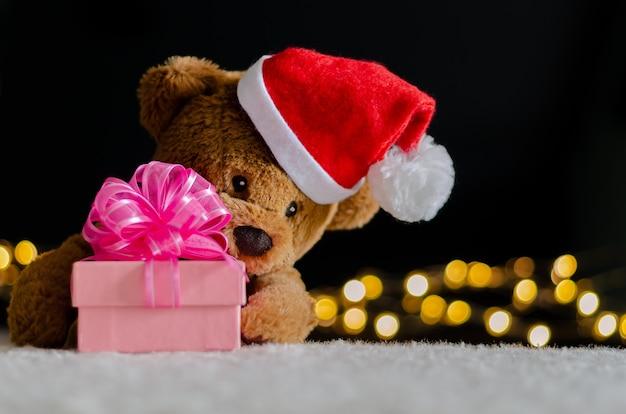 Плюшевый мишка в шляпе санта-клауса, держащей размытый фокус рождественской подарочной коробки. Premium Фотографии