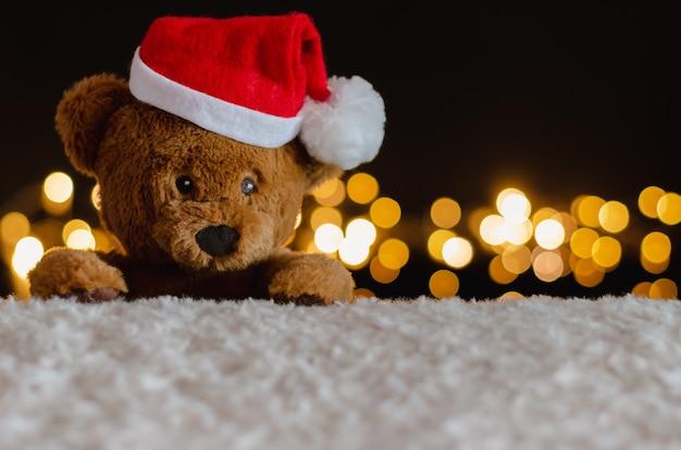 Плюшевый мишка в шапке санта-клауса с рождественскими огнями. Premium Фотографии