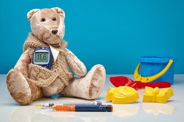 血糖値計とインスリン注射器のペンと青い壁に散らばった子供のおもちゃを持ったテディベア。小児、高血糖、小児科医における糖尿病治療の概念 Premium写真