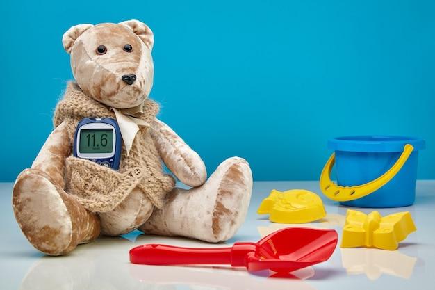 血糖値計と青い壁に散らばった子供のおもちゃを持ったテディベア。子供の糖尿病、高血糖症、小児科医の治療の概念 Premium写真