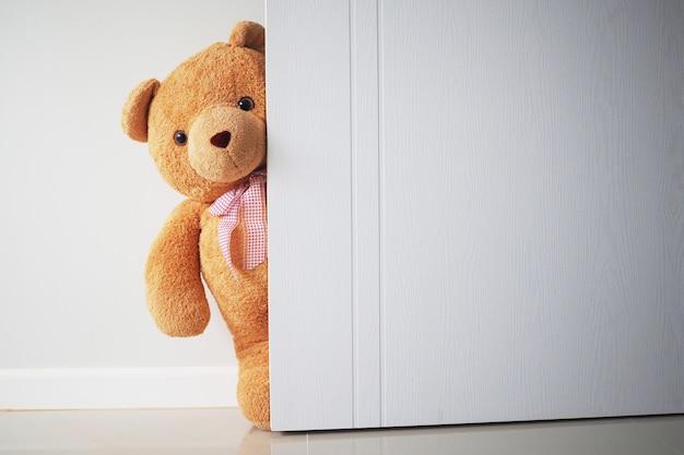 Teddy bear with brown hair behind open door. Premium Photo