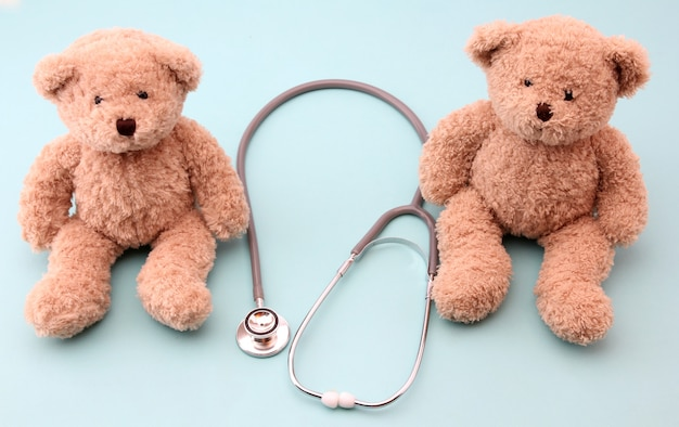 Teddy bears and medical equipment on blue Premium Photo