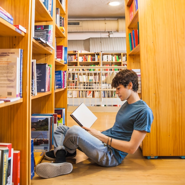 Teen boy leaning on bookcase and reading Free Photo