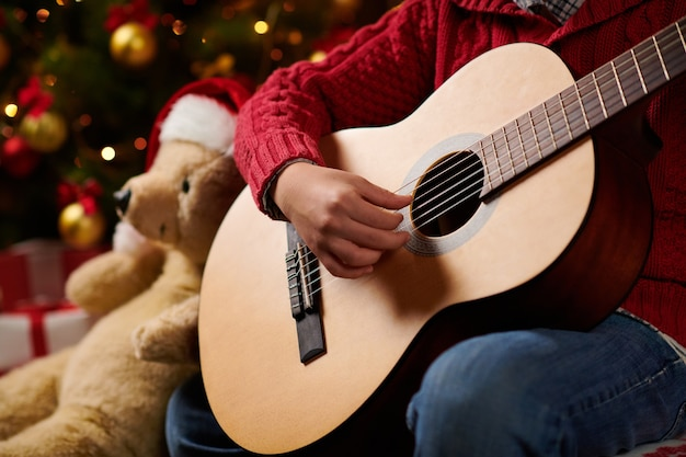 Teen boy playing guitar, sitting indoor near decorated xmas tree with lights, dressed as santa helper - merry christmas and happy holidays! Premium Photo