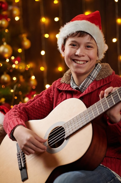 ライトで飾られたクリスマスツリーの近くに座ってギターを弾く10代の少年 Premium写真