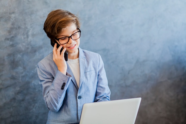 Teen boy talking over mobile phone and using laptop Premium Photo