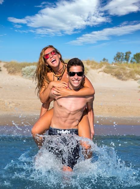 Teen couple enjoying  piggyback on summer beach Premium Photo